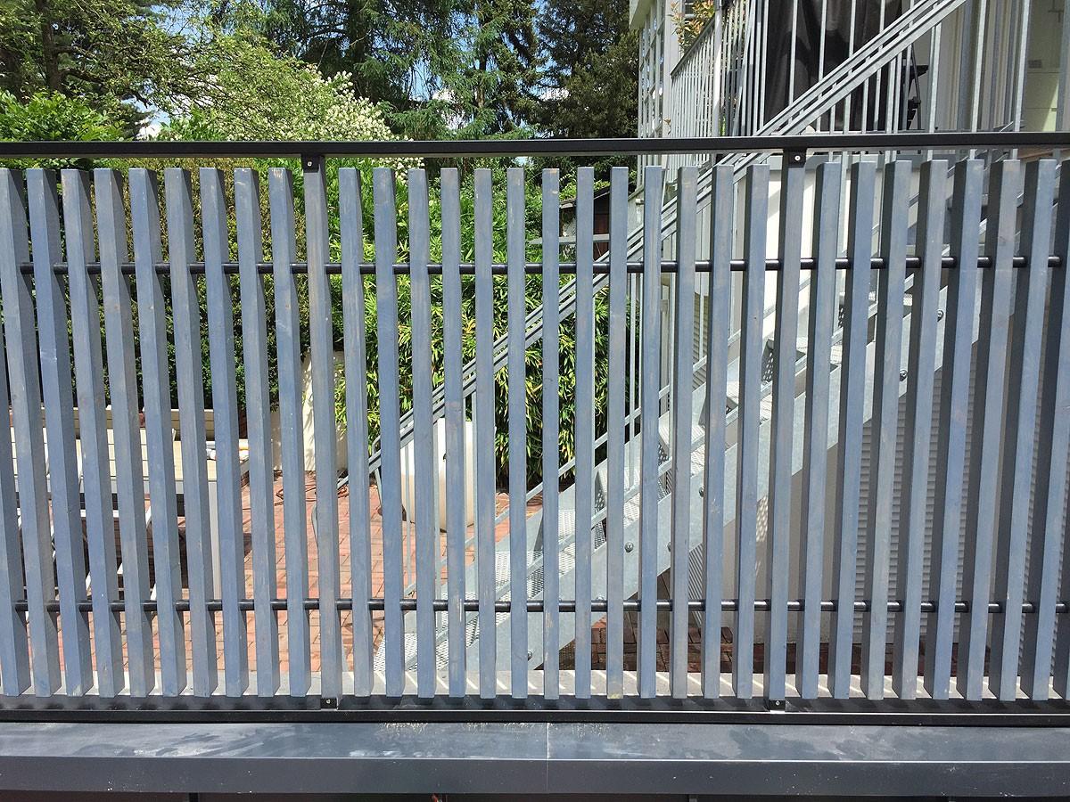 Detail aus Sichtschutz aus lasierten Lärchenholzbrettern in schwarzem Edelstahlrahmen.